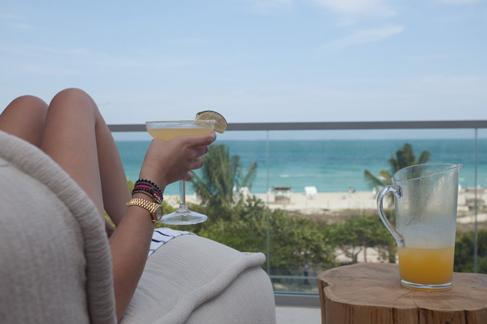 A woman relaxing looking over the beach with a drink in her hand