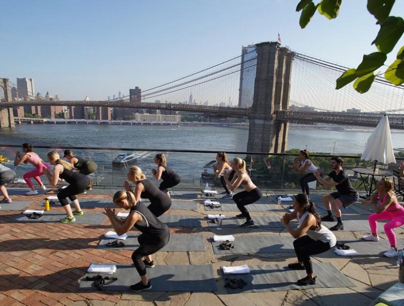 A group fitness routine being done with a view of the Brooklyn Bridge