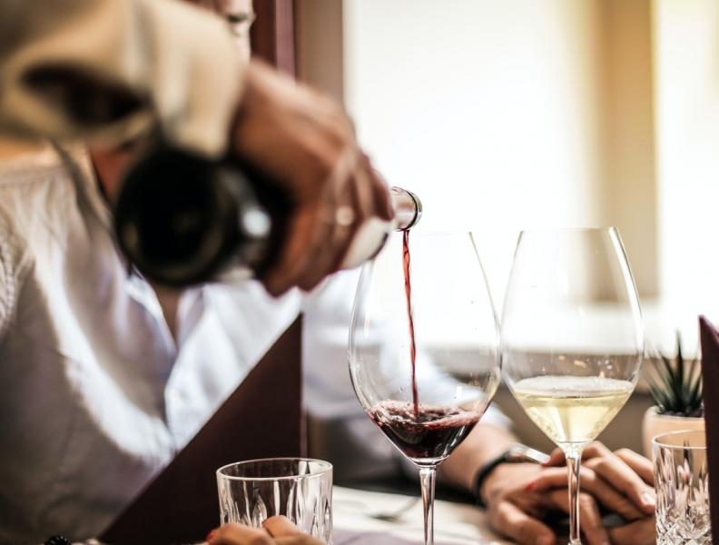 person serving red wine