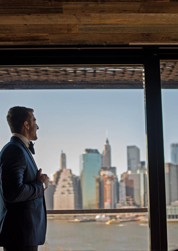 A bridegroom staring out a window with a view of the Manhattan skyline.