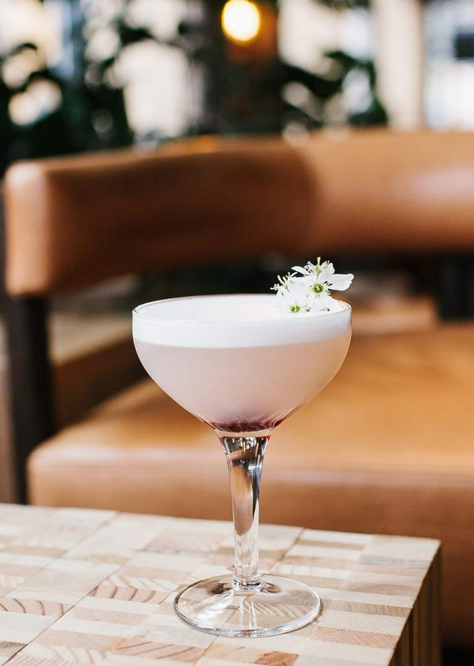 fancy pink cocktail with flower in cupe glass