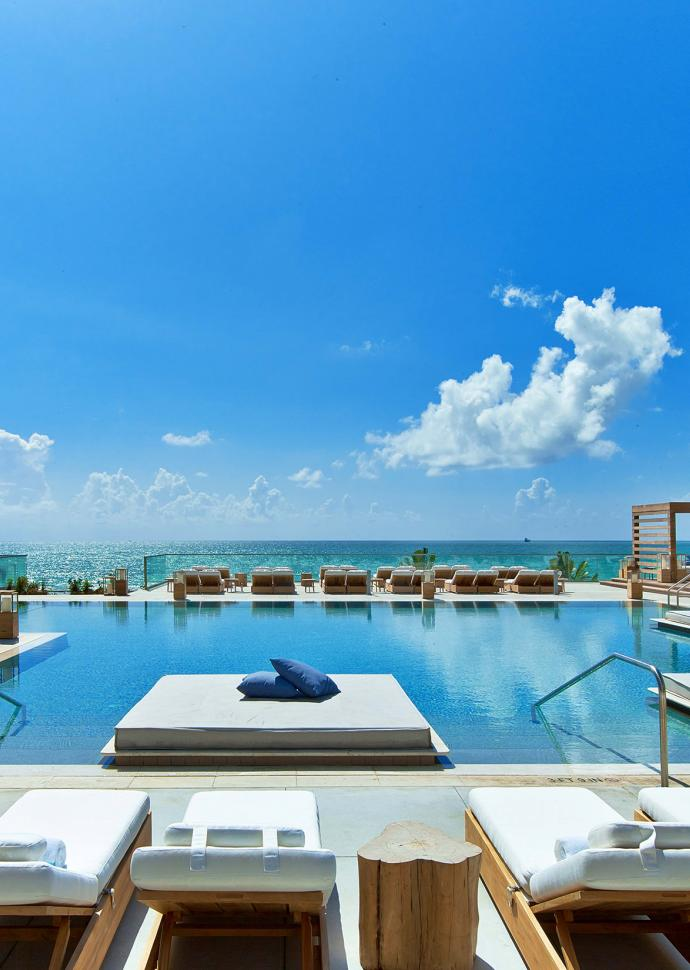 South Beach pool surrounded by cabanas and day loungers