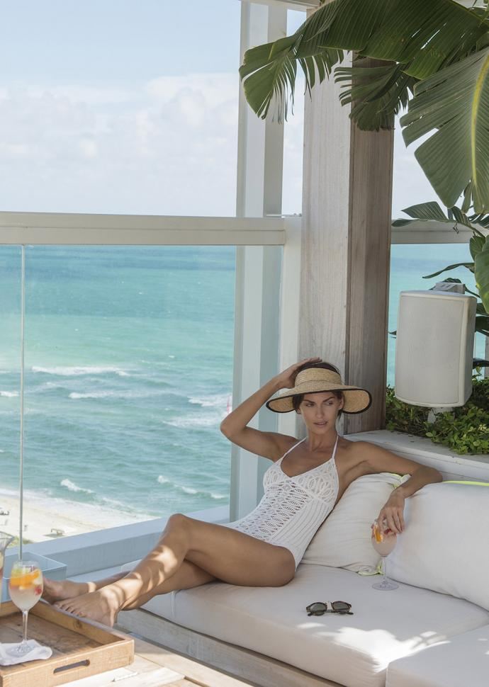 woman in bathing suit and hat relaxing in cabana with white sangria