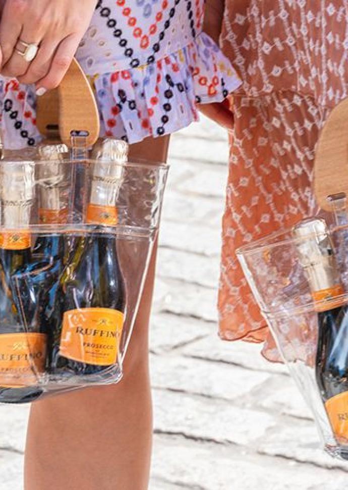 Girls holing bags full of prosecco bottles