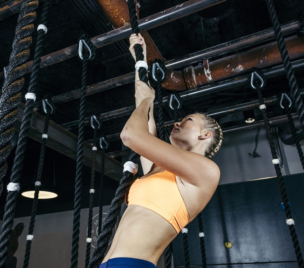 Woman climbing rope at spartan gym