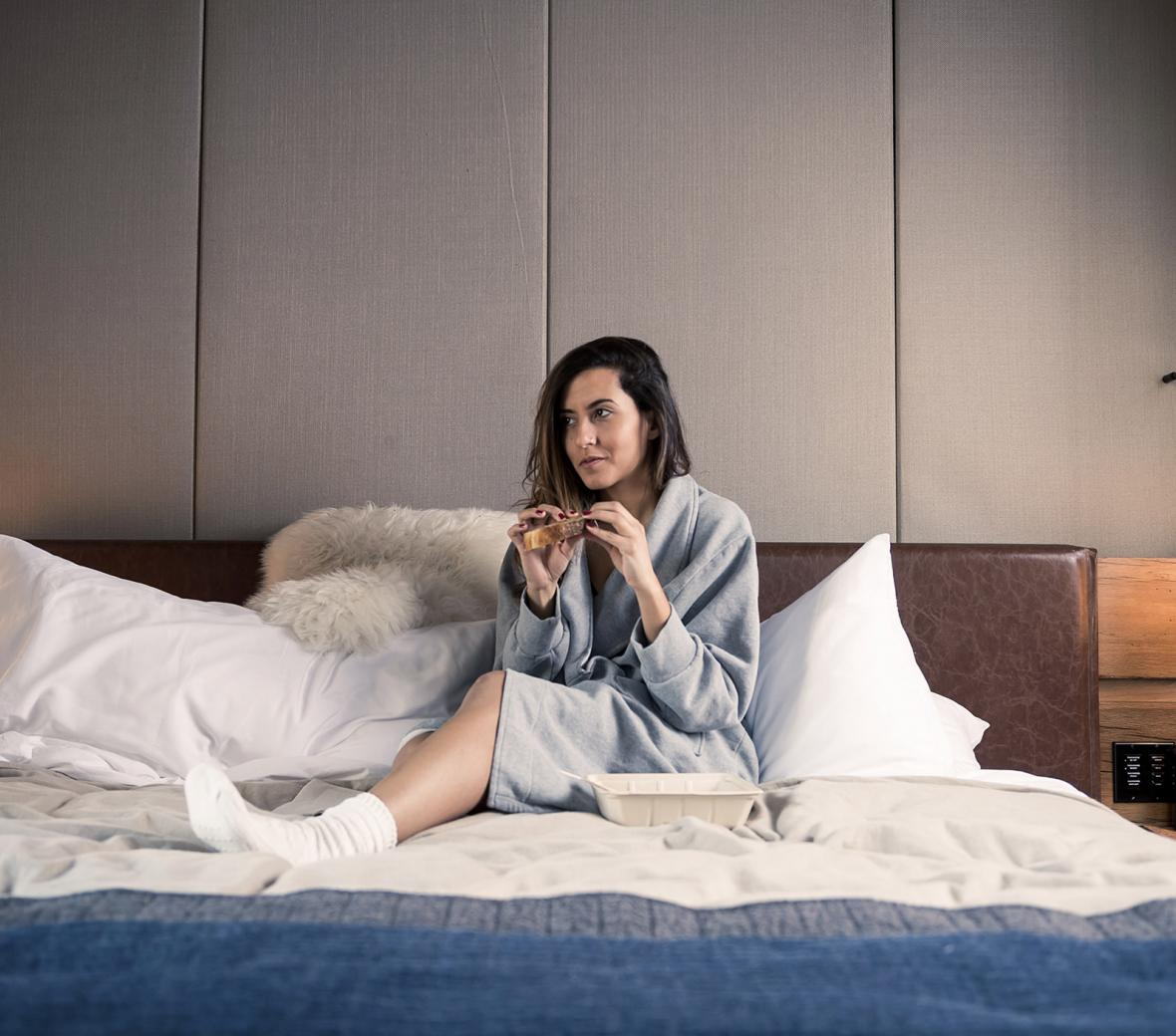 Woman in bed with coffee in bathrobe