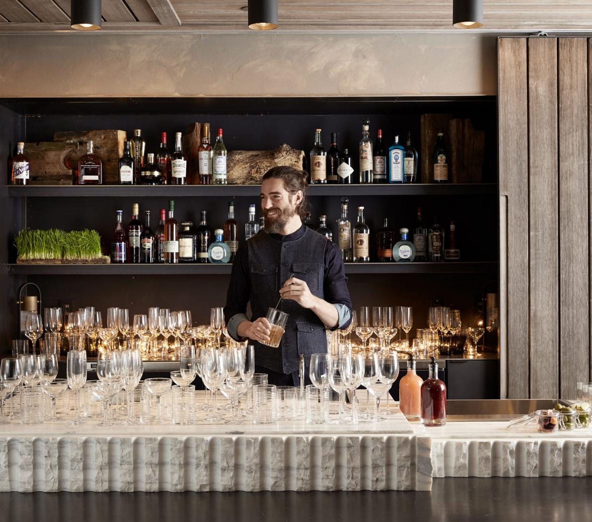 Bartender making cocktail in front of fancy bar