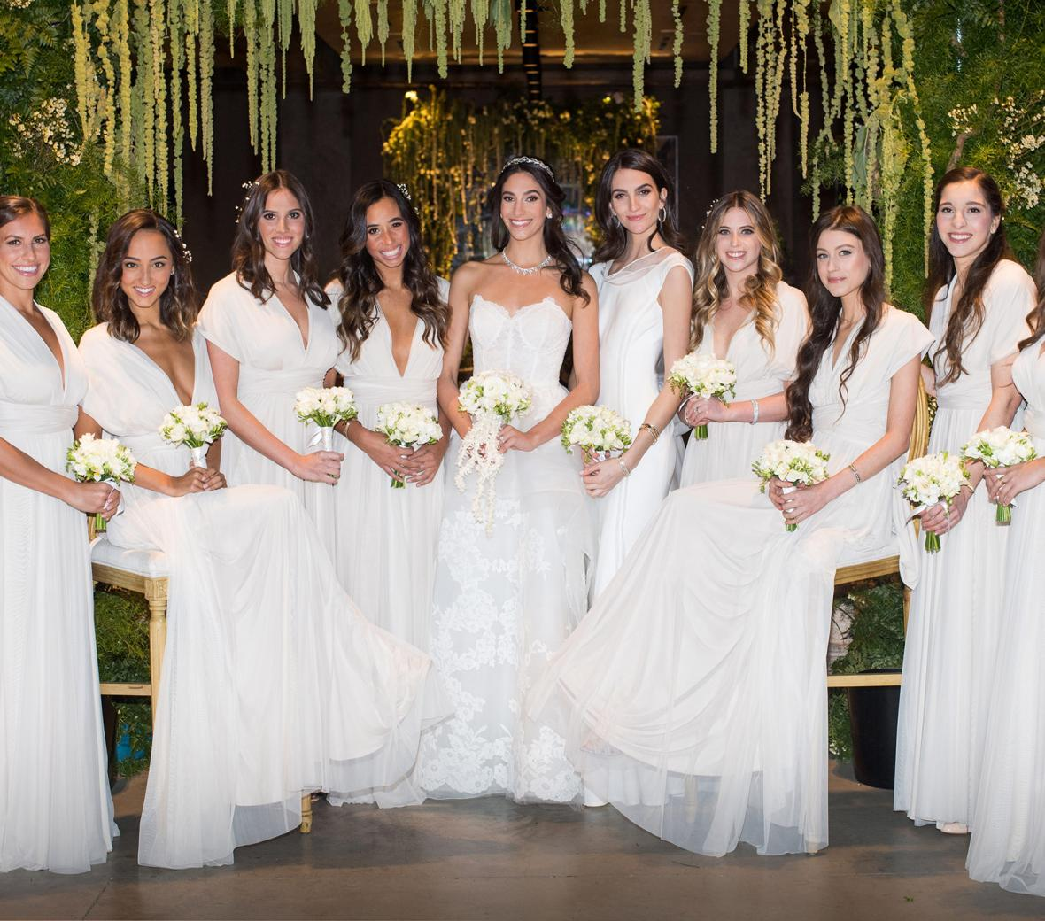 A bride and a row of bridesmaids all wearing long white dresses.