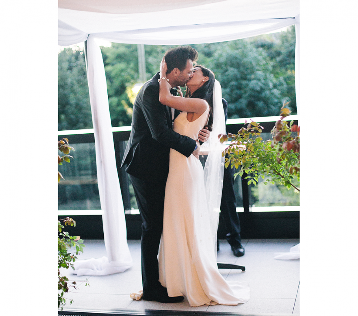 A bride and groom kissing in an outdoor wedding venue.
