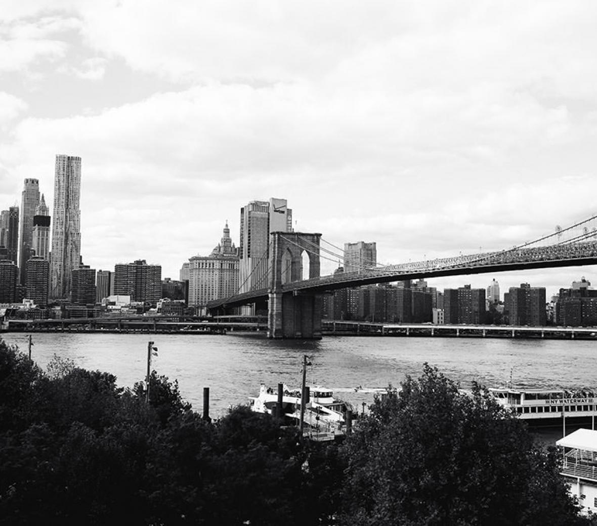 A black and white image of the Brooklyn Bridge and Manhattan skyline.