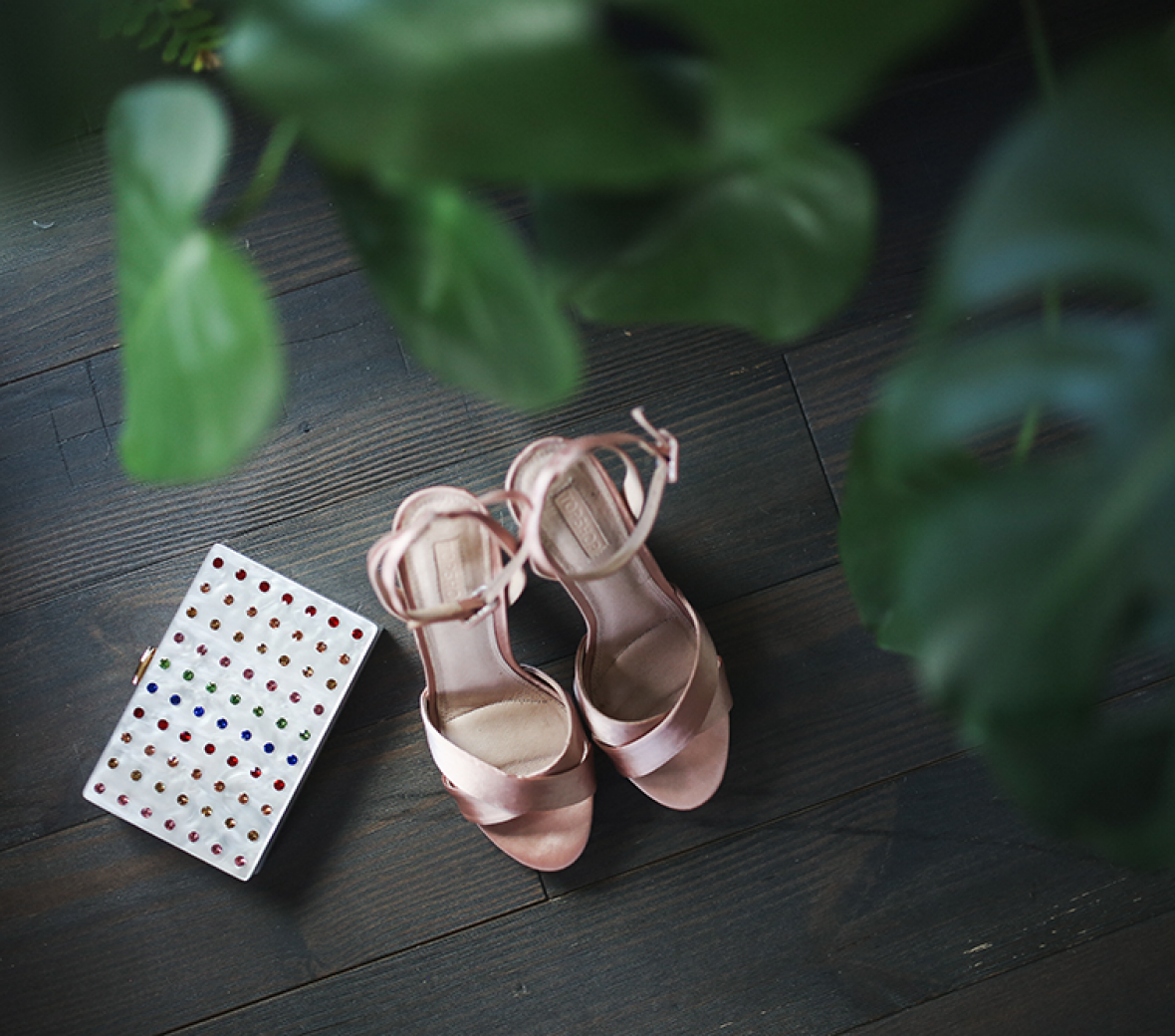 Pink satin high heel slippers and a jeweled clutch on a wooden table.