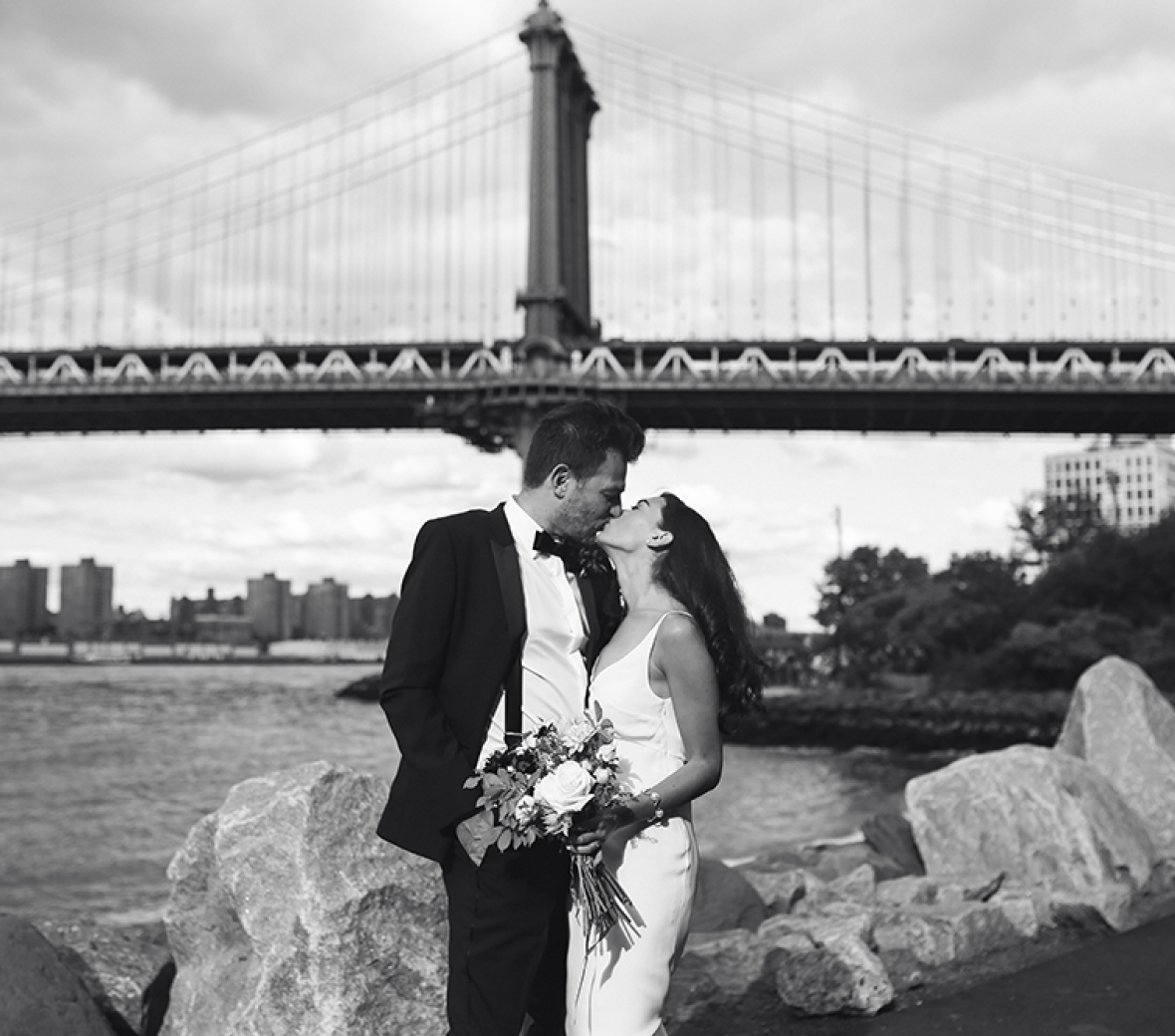 A black and white image of a bride and groom kissing at the Brooklyn Bridge.