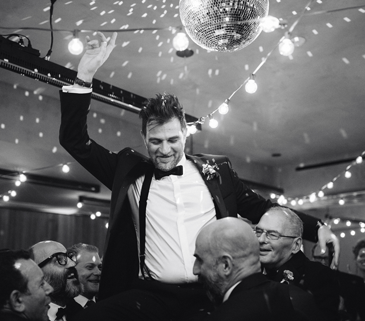 A black and white photo of a groom celebrating on the dance floor.