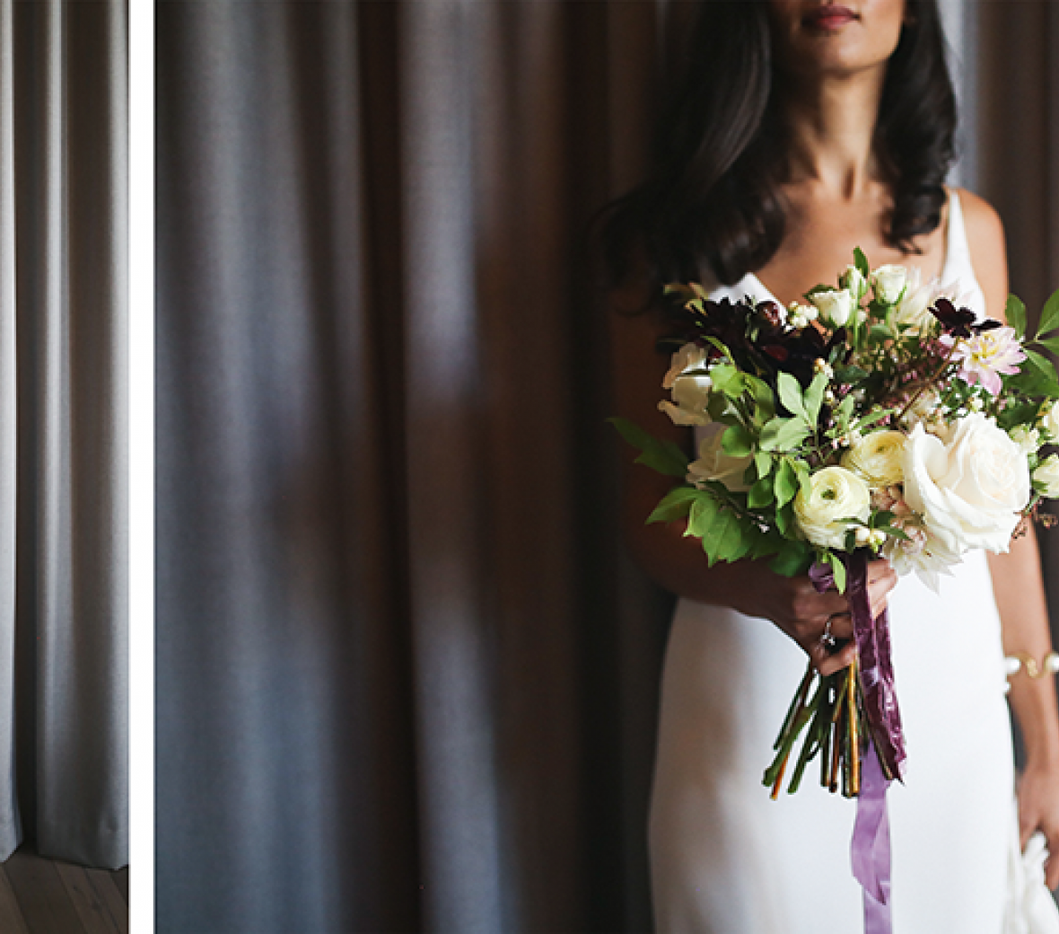 A bride in a long white dress with a bouquet in front of charcoal grey curtain.