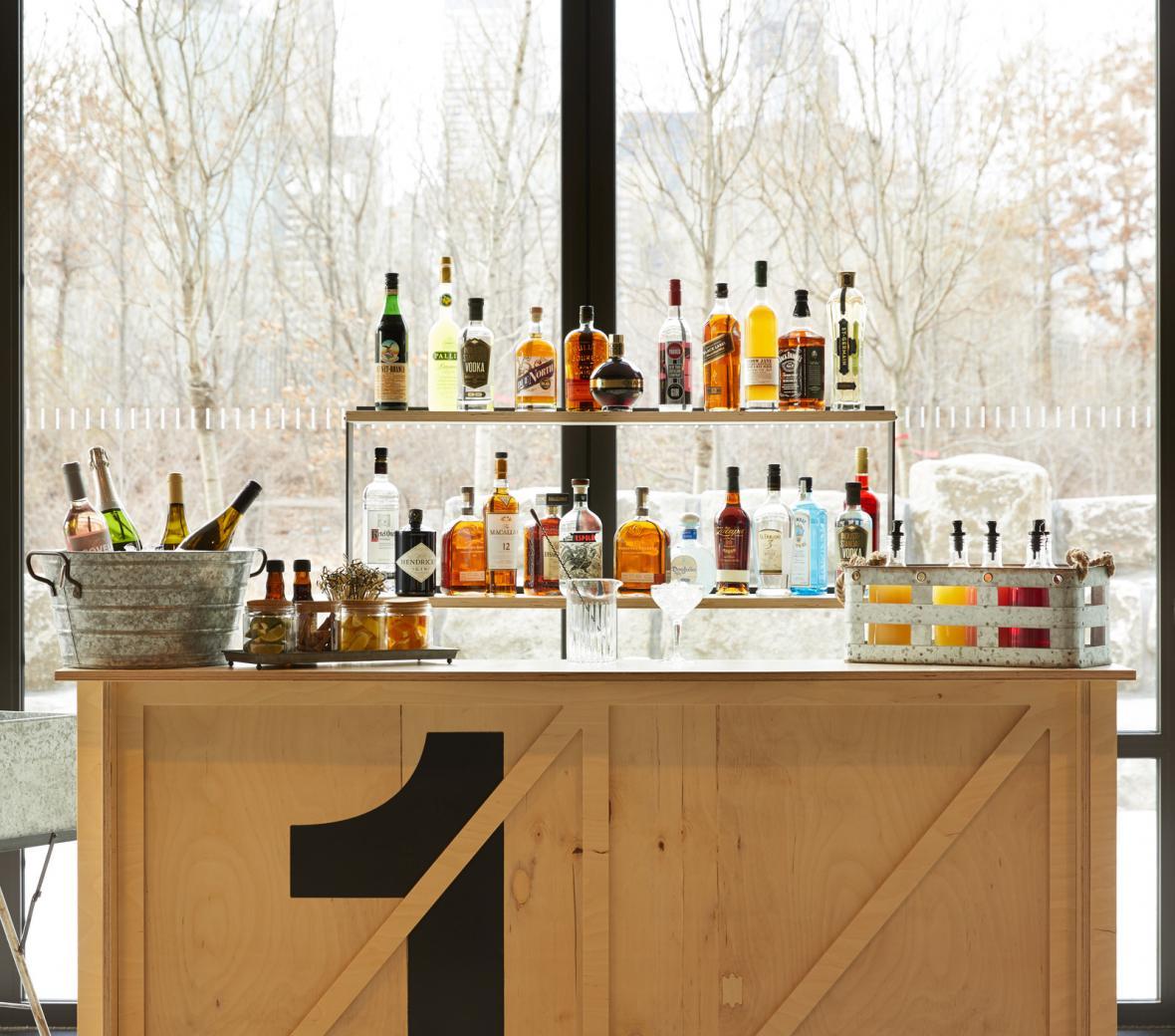 A wooden lobby bar with an array of liquor bottles at 1 Hotel Brooklyn Bridge.