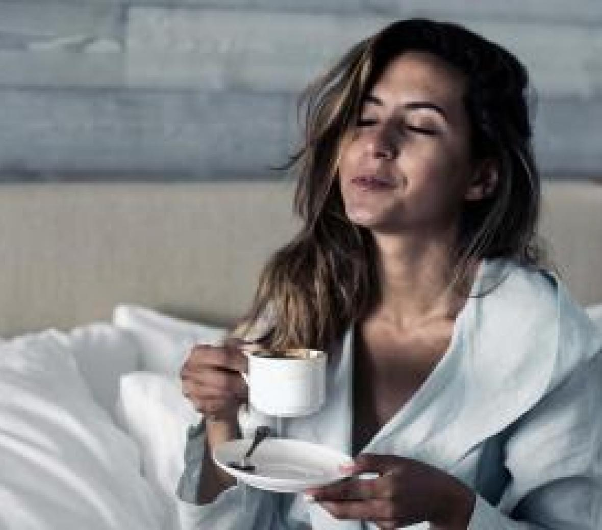 A woman sitting on a bed drinking coffee