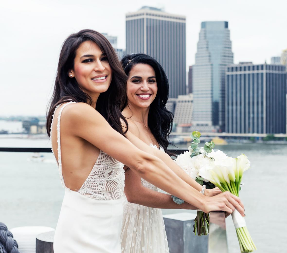 A bride and her maid of honor on a rooftop with a view of Manhattan.