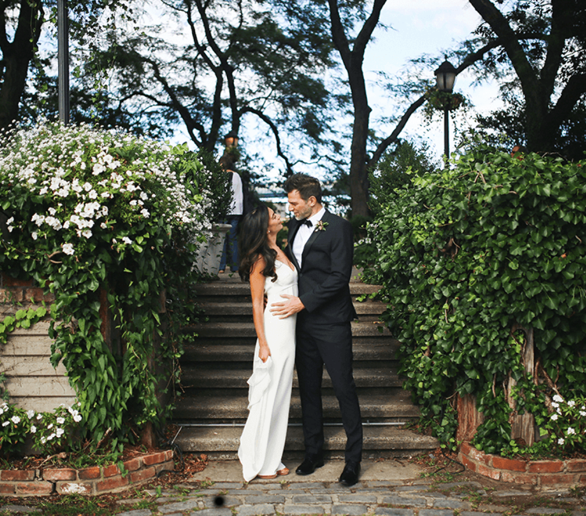 A bride and groom standing by steps and staring into each others' eyes