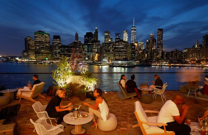 The Rooftop at 1 Hotel Brooklyn Bridge at night with view of Manhattan skyline