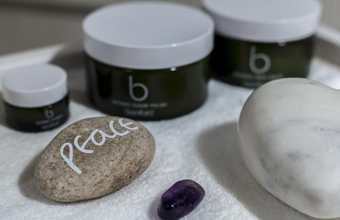 "A rock painted with the word ""peace"" sits next to some spa products"
