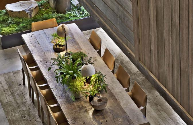 A long wooden table decorated with plants at 1Hotel Brooklyn Bridge