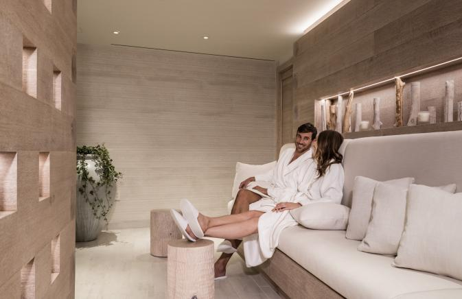 A man and woman in white robes and slippers chatting in a spa waiting area.
