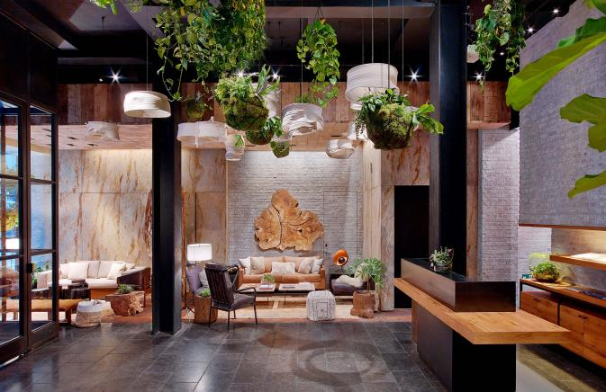 The lobby of 1 Hotel Central Park, furnished with wood and greenery
