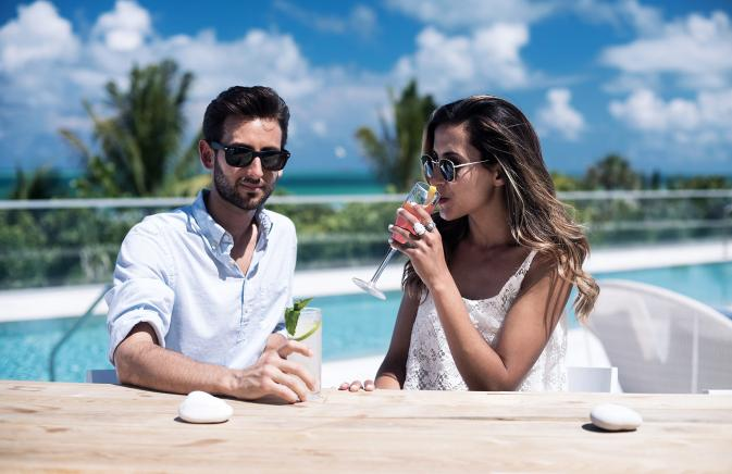 Couple sipping cocktails in front of a pool