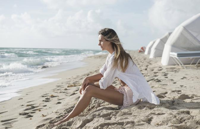 woman sits on beach staring into the water