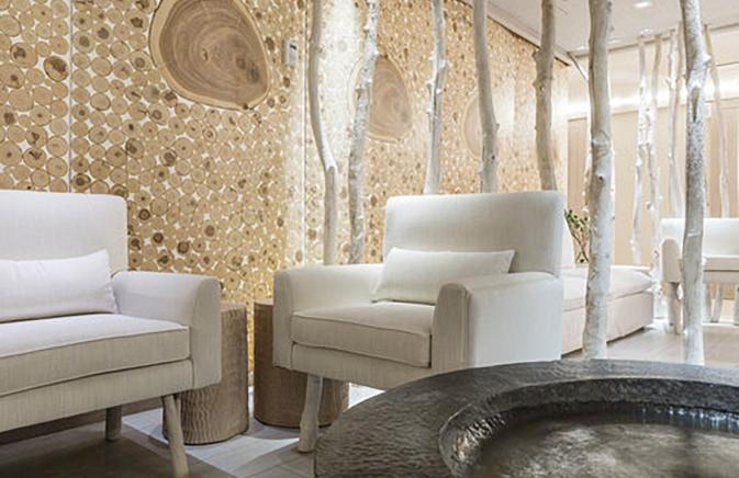 White chairs and a water feature in the waiting area of Bamford Haybarn Spa.