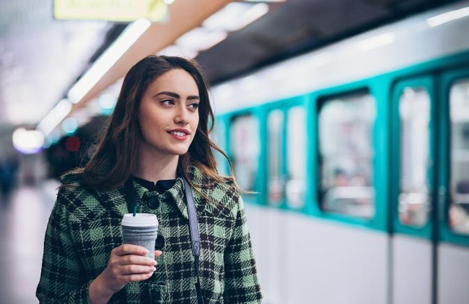 Woman holding coffee waiting for subway