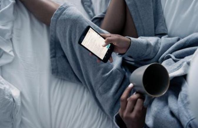 Person in bed reading phone with coffee
