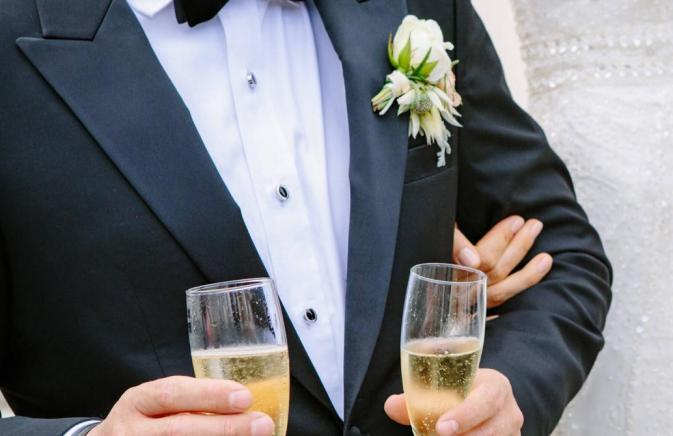 man in tux carrying champagne glasses