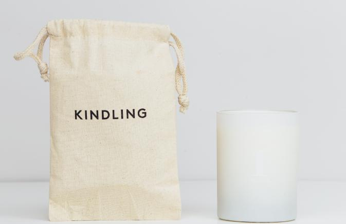 A white candle next to a beige bag that says 'kindling'
