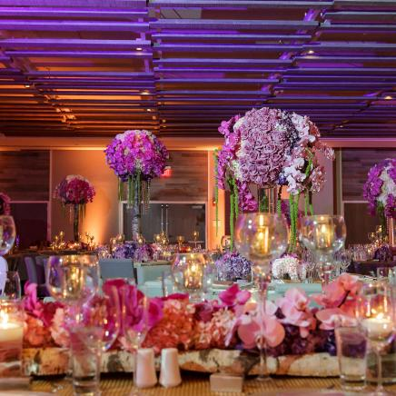 Banquet tables with floral arrangements in ballroom at 1 Hotels South Beach for wedding