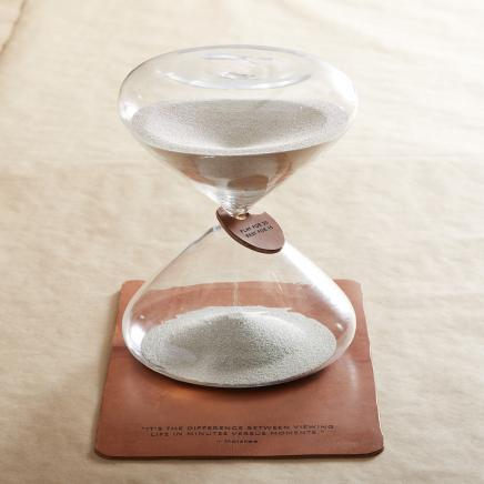 hourglass with sand on leather notebook