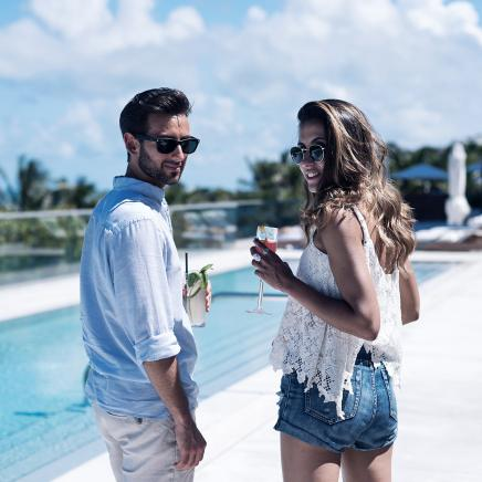 Couple walking along pool with cocktails