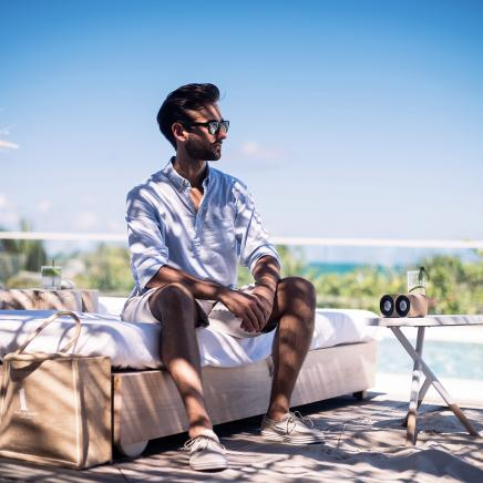 A man dressed in a casual white linen shirt sitting poolside on a cabana bed.
