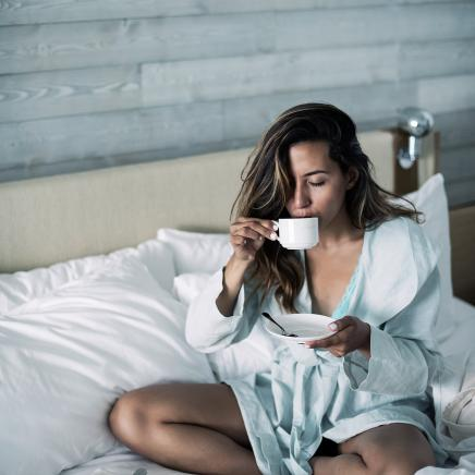 Woman sipping tea and eating pastry in bed