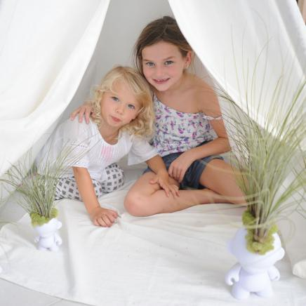 Two little girls peek out of a small tent