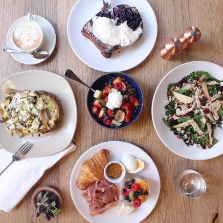 Bird's eye view of breakfast dishes with croissants and coffee and fresh fruit from Jams