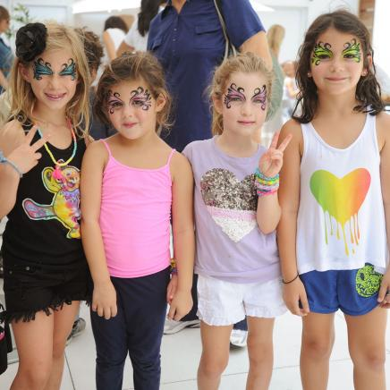 Little girls with butterfly face paint smile for the camera