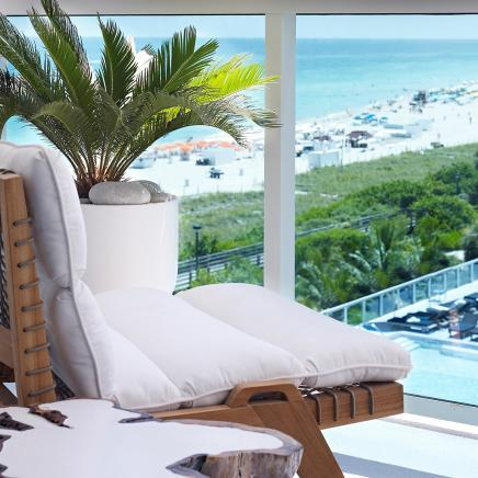 wooden chair with white cushion on balcony over looking pool at 1 hotels south beach