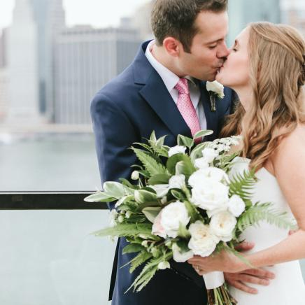 Couple kiss in front of Brooklyn Bridge