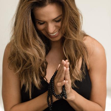 Sabrina from Kanekshun holding hands in prayer pose with mala beads