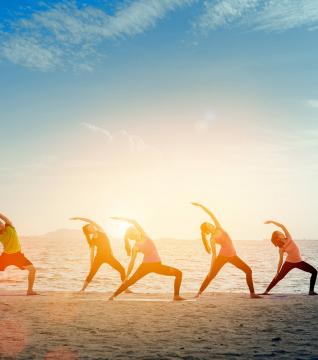 group doing yoga on the beach