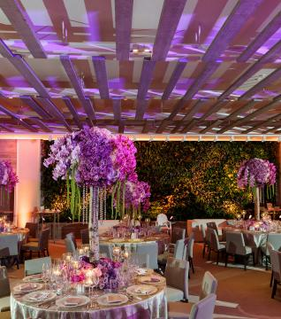 Wedding ballroom with floral arrangements on tables and pink and purple mood lighting