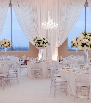 A banquet hall decorated with white linen and flowers