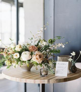 A round wooden table decorated with wedding florals and tealights.