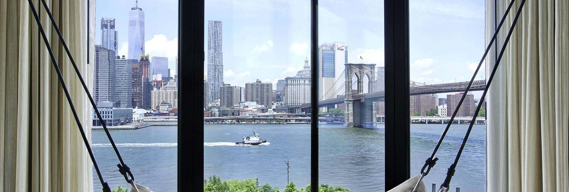 A hammock hanging in a 1 Hotels suite with a view of Brooklyn Bridge.